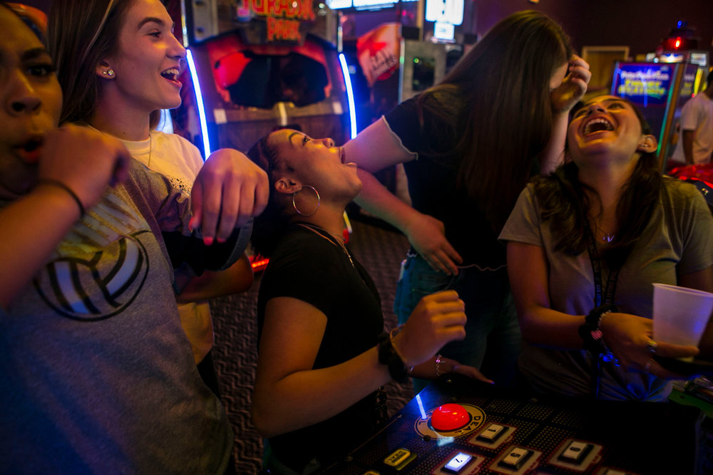 Reactions erupt as Jevani Hanspard, 16, center, loses a game as the group celebrates making the first ever Harlan High School varsity volleyball team at Peter Piper's in San Antonio.