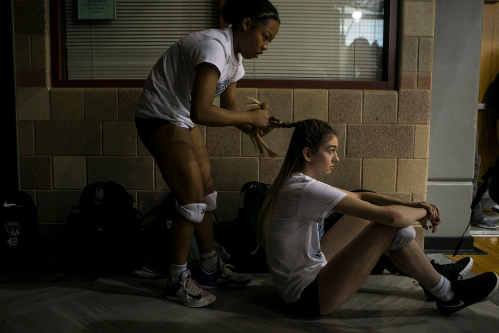 In a quite momement before their game Jevani Hanspard, 16, braids Kiana Fallaha's, 15, hair before the Harlan High School varsity volleyball team's first scrimmage at Reagan High School. Hanspard has become the team's designated braider and multiple players call on her to help keep their hair out of their face as they play.