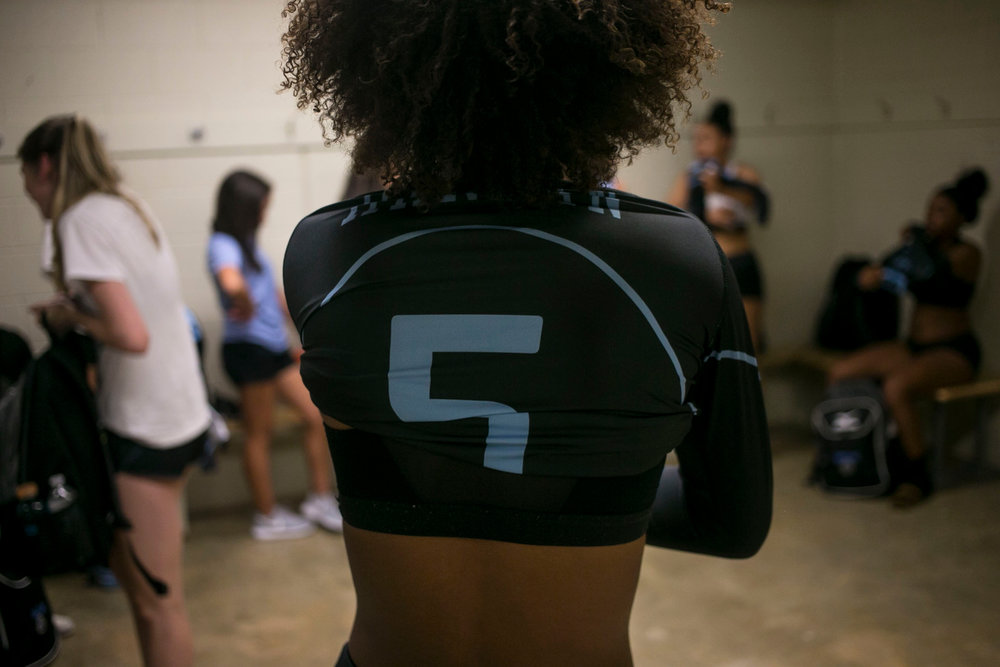 Ayanna Jackson, 16, pulls on her uniform as she prepares for the first Harlan varsity volleyball game at Paul Taylor Fieldhouse.
