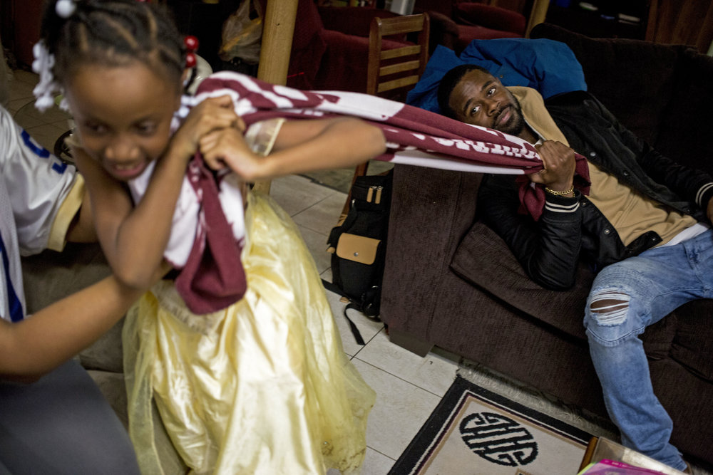 Deontè Gardner plays his his sister Jade Gardner, 6, in the basement of his dad's house in Chicago, Ill.