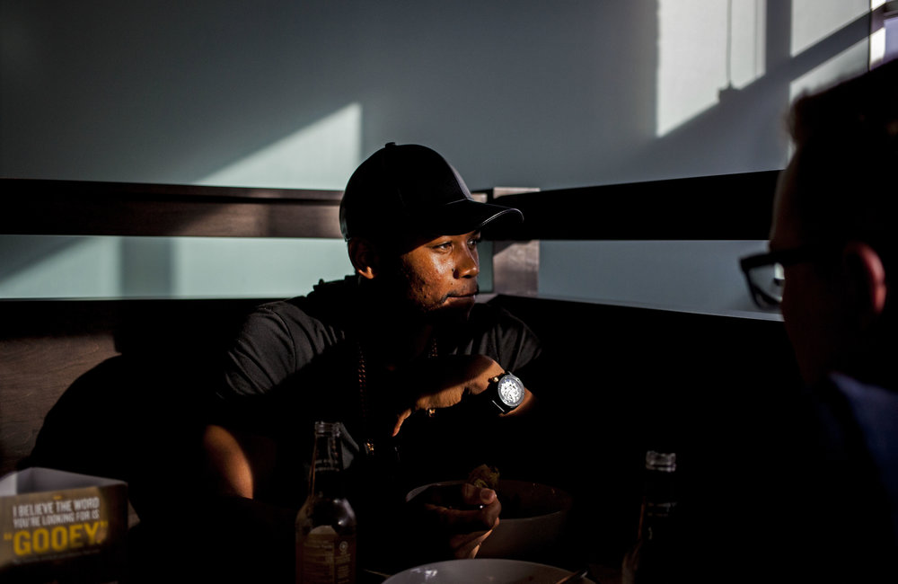 """While meeting with a friend for dinner, Aaron Johnson looks out the window as he thinks about what they are talking about. As a musician and rapper, Johnson uses his platform of music to make a difference. """"I have a responsibility to speak up on this… (but) there's a lot of grace that has to be involved,"""" says Johnson."""