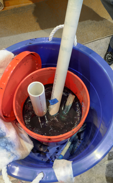 Pole-wrapped silk soaking in the vat of indigo dye