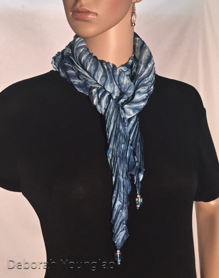 Pleated shibori silk satin scarf with beaded tips.. Pleated size approx 7 x 56 in., original size 14 x 72 in.
