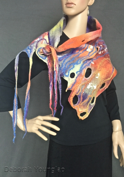 Sunset colors in this asymmetrical piece. There are holes at one end and 'dreads' at the other end for threading through the holes and tying. Merino wool and wool yarn.