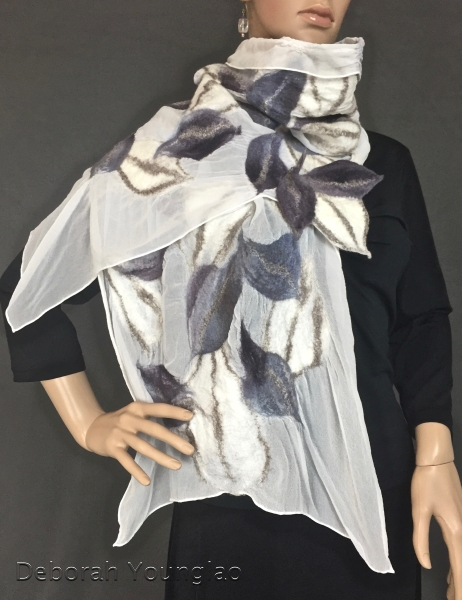 Neutral colors in this one. Blue-grey and white merino leaves, enhanced with silk and champagne colored yak fibers, are felted onto silk chiffon.