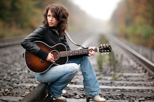 """Carrying on her immense folk legacy with unique grace, Sarah Lee Guthrie brings an open heart and true purpose to her recently-launched solo career. Mondays at her Dad Arlo's church in western Massachusetts, she has started The Hoping Machine,a gathering of local activists and singers who workshop songs specifically for marches and rallies. Whether she's marching along side you and me or finding her place in the spotlight on stages across the world, this woman charms and inspires as you can see in thisvideo of her song """"Overcome."""""""