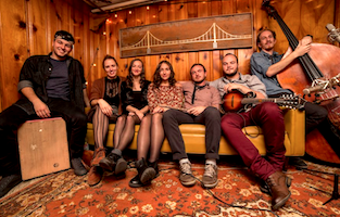 This acoustic septet from Upstate New York is a sonic whirlwind of foot-stomping Americana, complete with mandolin, alto/baritone saxophone, cajon, and upright bass, all led by a soaring harmonic trio of powerhouse female vocalists. We're sure hope Upstate Rubdown will enjoy their first Hoot and you'll be dancing along on Hoot Hill. Check out this sweet video-it makes us wanna hear them sing in the Pewter Shop!