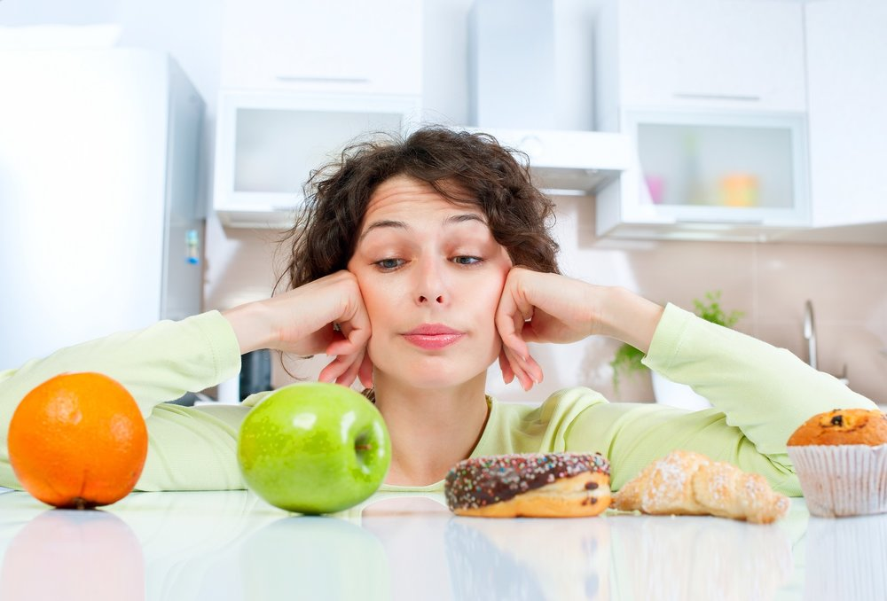 Woman choosing between healthy fruit and pastries