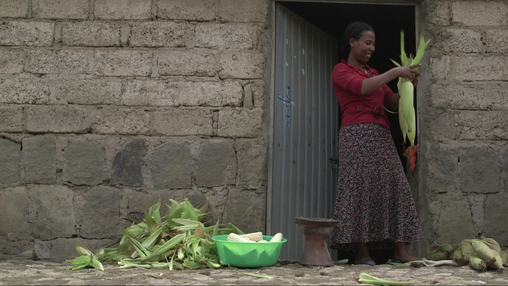 Salam prepares corn to roast and sell in front of her house.