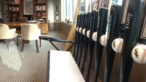 A White Sox-themed bench made of baseball bats featuring family members' names sits in Andrew Berlin's West Loop office.