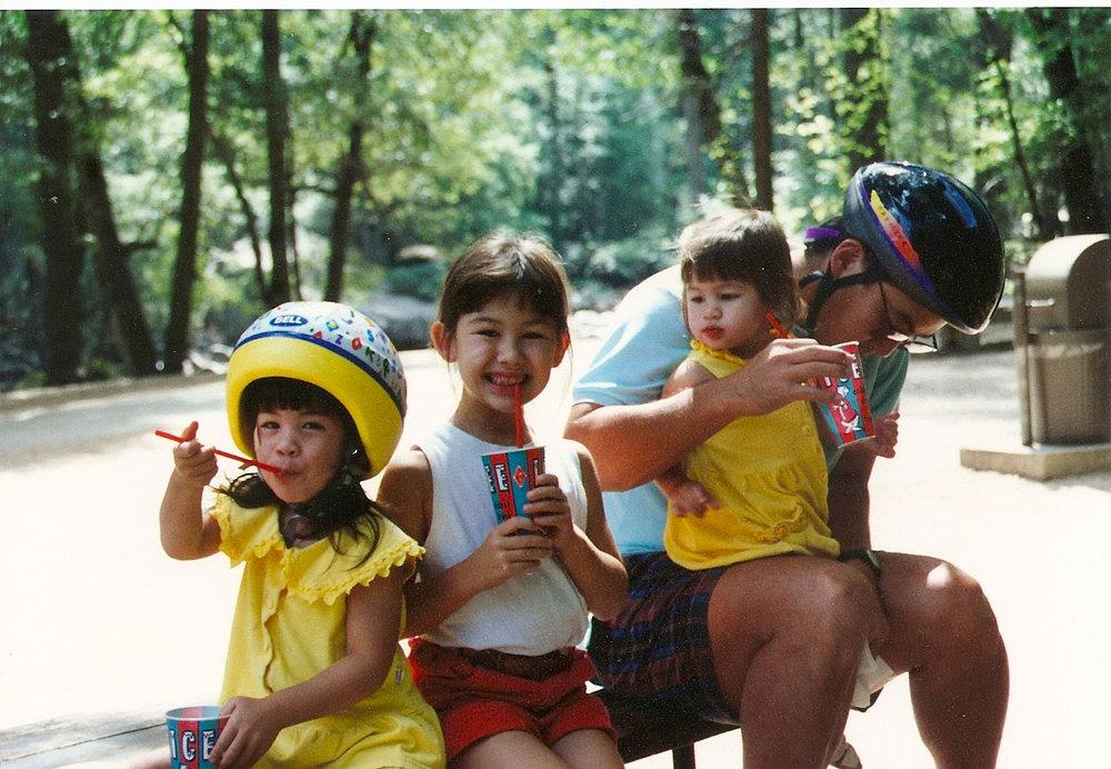 Kristen (left), age 3, enjoys an Icee in her helmet.
