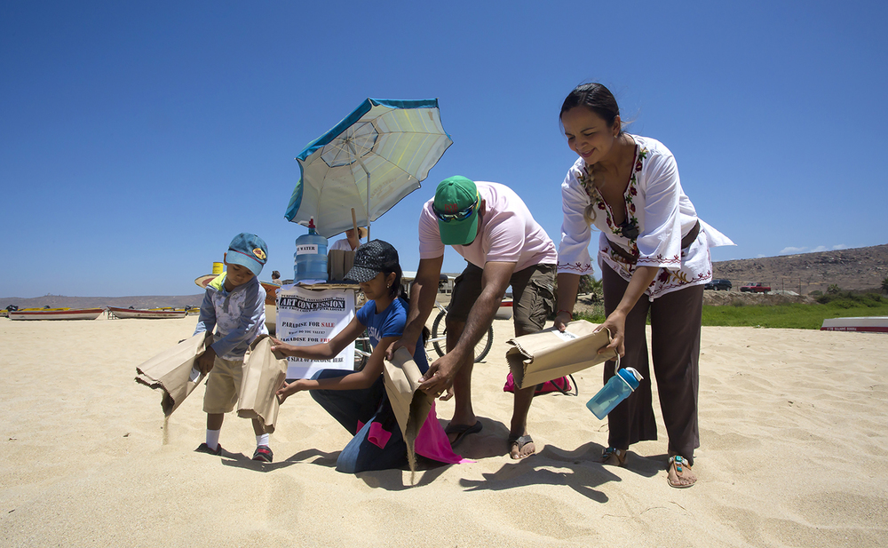"A family makes the symbolic gesture of restoring the land, by engaging in the activity of ""dune building."""