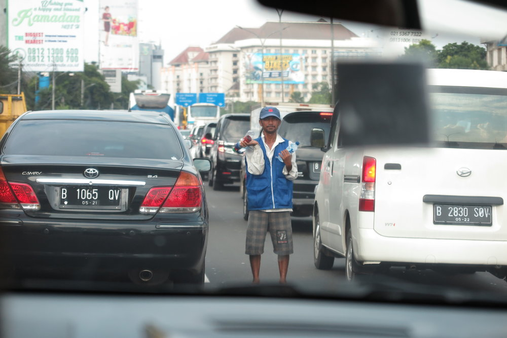 A guy selling water in heavy traffic in Jakarta. The cars are going so slowly that people sell all sorts of stuff by standing in the middle of the highway.