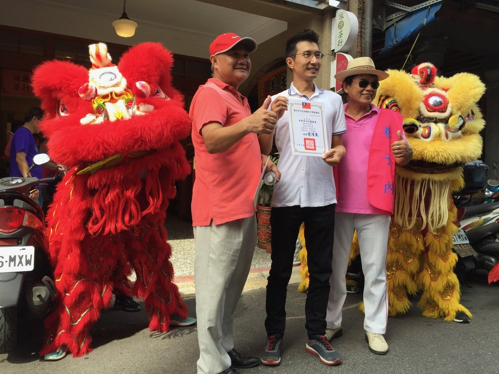 Dragon and lion posing with Lee Bakery owner, Mr. Lee, after they blessed his shop with a dance
