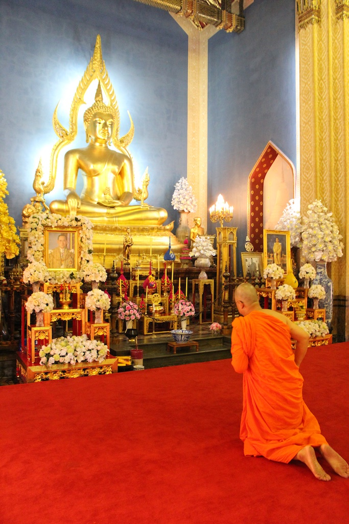 A monk in robes prays to the Buddha inside the White Marble Temple