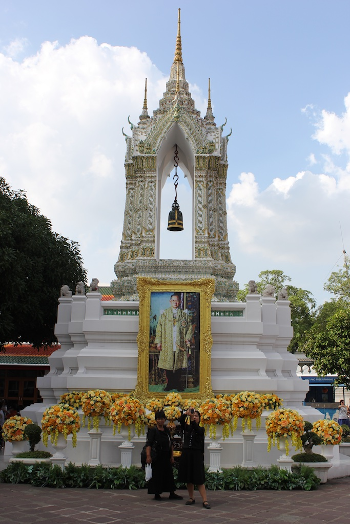 A portrait of King Bhumibol Adulyadej inside the Wat Pho temple complex. Note the folks in front, dressed in black.
