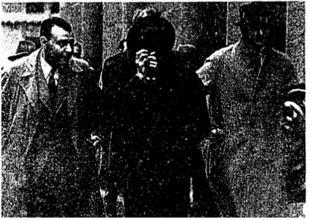 """Riley Finally Rearrested  After hiding from the United States authorities for almost four months.Jack Riley was finally rearrested on March 28, when detectives from the S.M.P., accompanied by Chief Deputy U.S. Marshal Sam Titlebaum and members of the Japanese Consular Police and Gendarmerie, raided a boarding house in Young Allen Court where they found the wanted man hiding in a Japanese woman's room. Said Riley; """"O.K.,boys, all's up,"""" when ordered to surrender. The photo shows Mr. Titlebaum,Riley,hiding behind his hat, and InspectorJ. G.Crighton, who was in charge of the detective party. (N.C.D.N. photo)"""