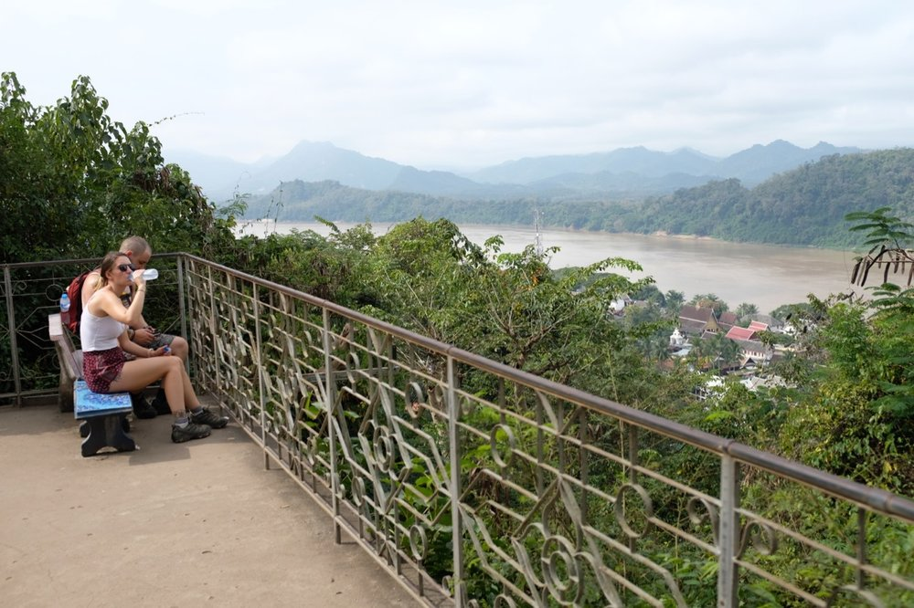 A pair of tourists take in the view from atop Mount Phu Si, looking out over the Mekong River and the town below.