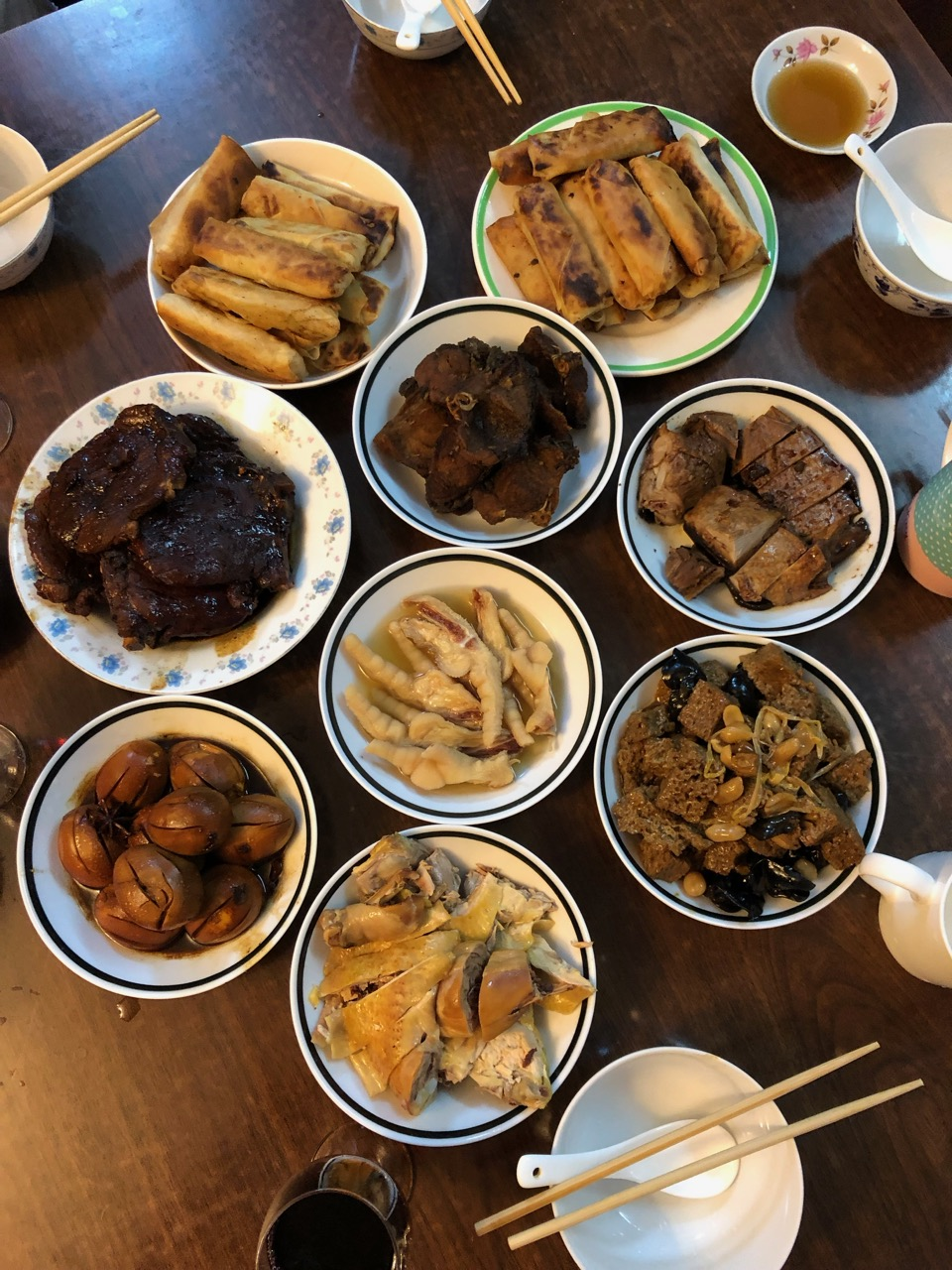 A classic Shanghai-style New Year's dinner cooked by my father-in-law: spring rolls, duck, chicken, fish, eggs, kaofu, pork chops, and chicken feet!
