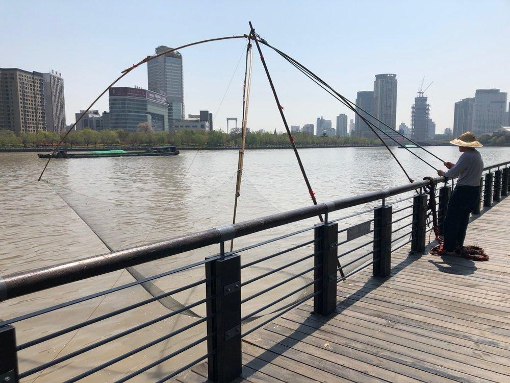 A fisherman casting his net along the Ningbo riverside