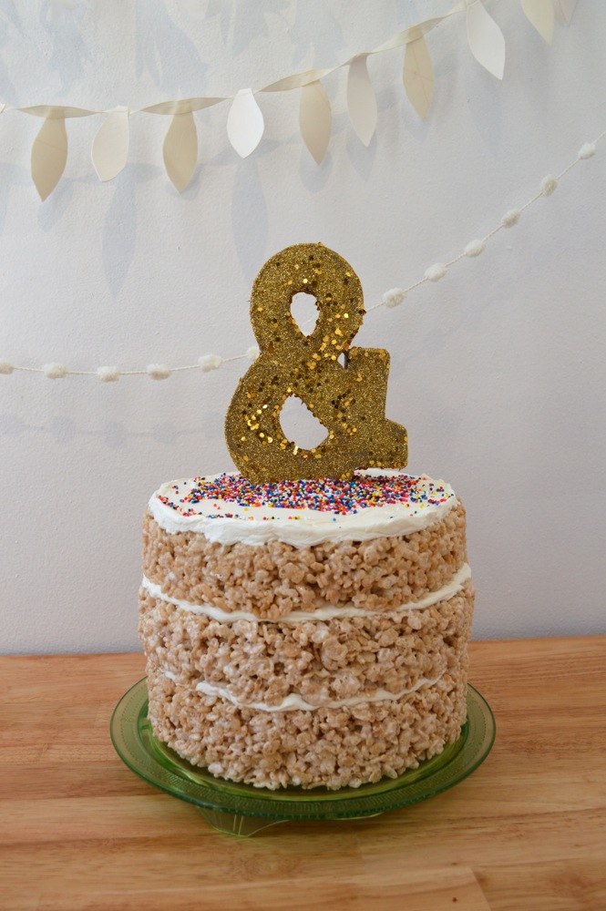 A naked cake made from layers of rice krispie treats, vanilla frosting, colorful sprinkles, and a glittery gold ampersand topper.