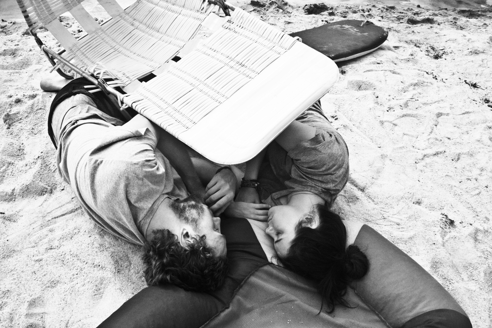"Punch Drunk Bush Love   ""This is a photo of two of my dearest friends, who found themselves, after a long weekend festival that we had organized, curled up on the beach at my house, with one of the deck chairs as shade and a floaty as a pillow.  They have such a beautiful love, and I love that I was able to capture of a piece of it."""