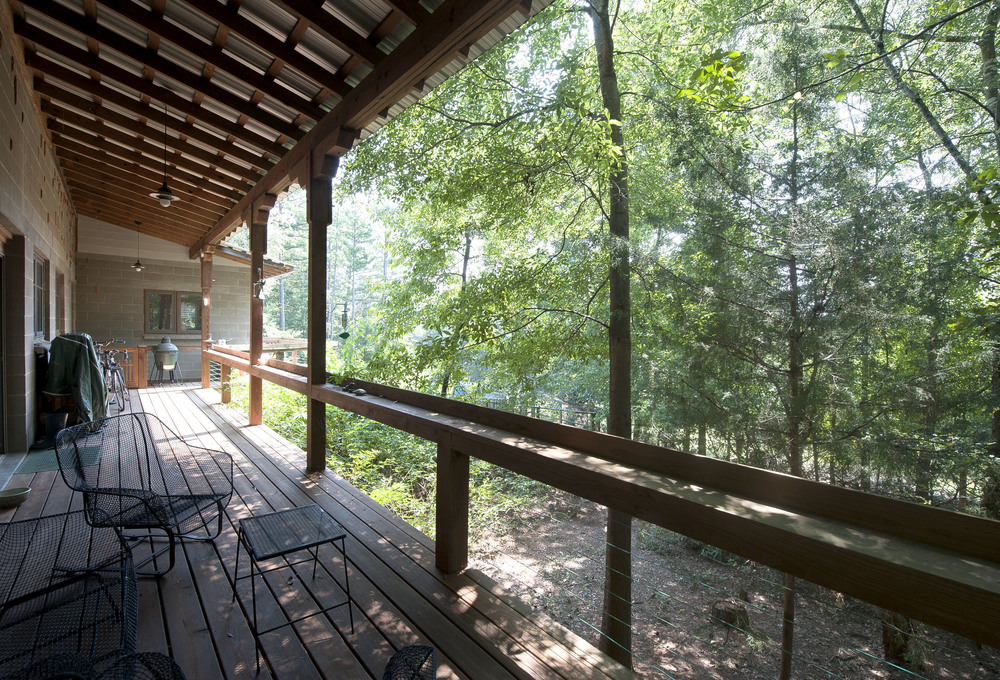 Covered back porch has a beautiful view of woods.