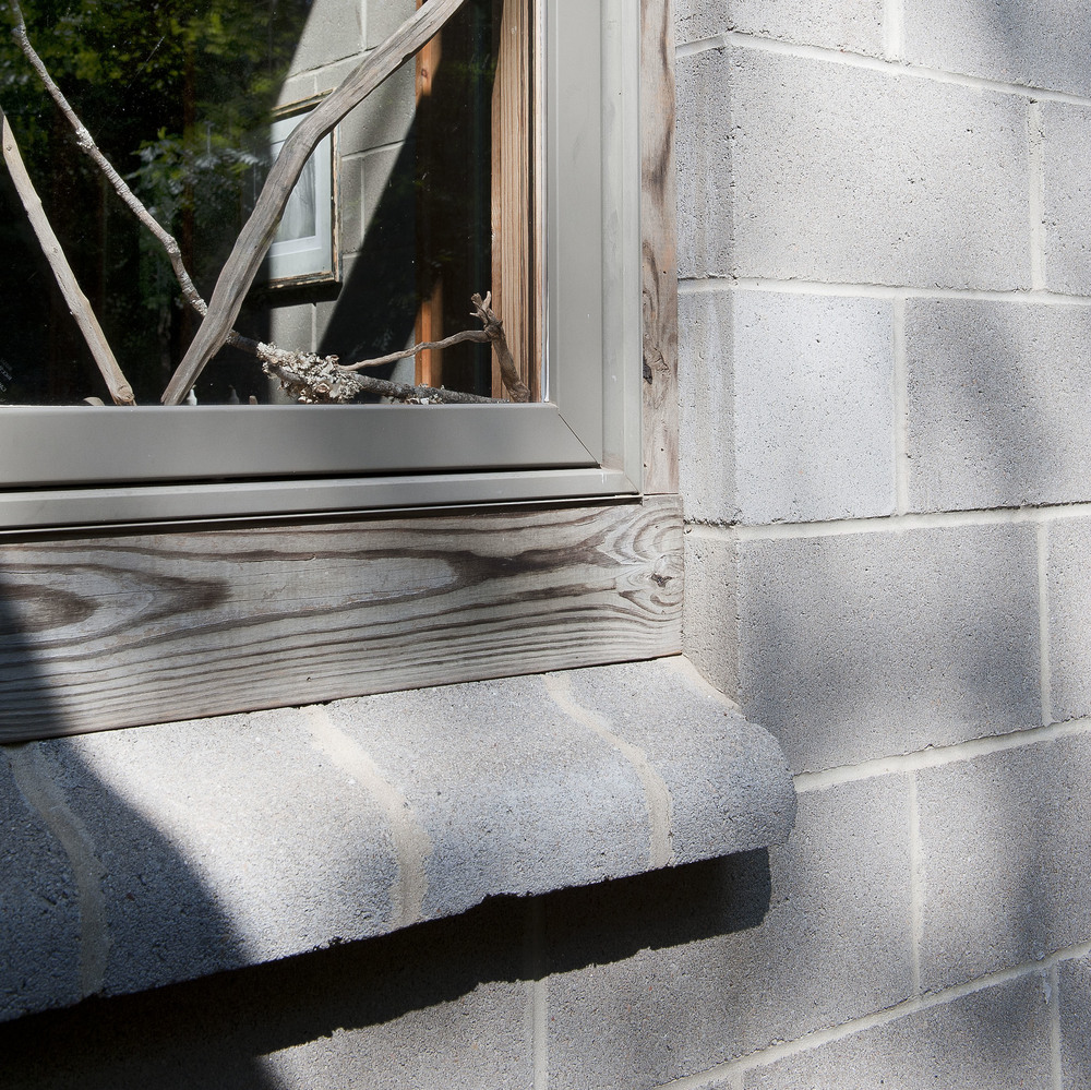Custom concrete block windowsill enhances natural wood frame.