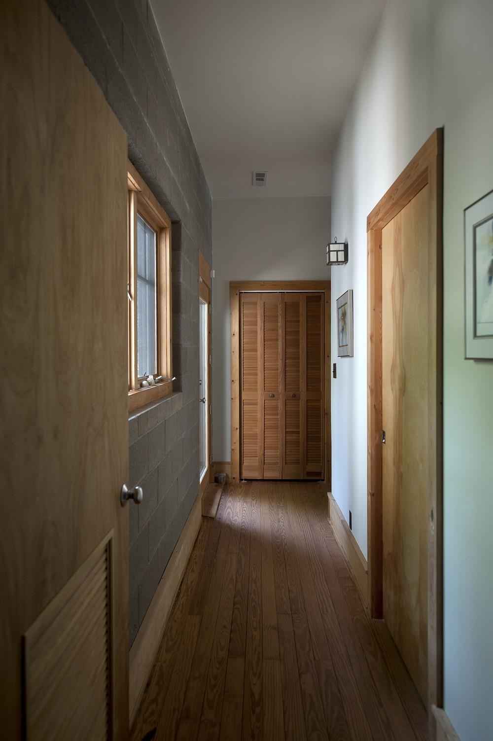 Custom woodwork, doors, and windows enhance the hallway to the office.
