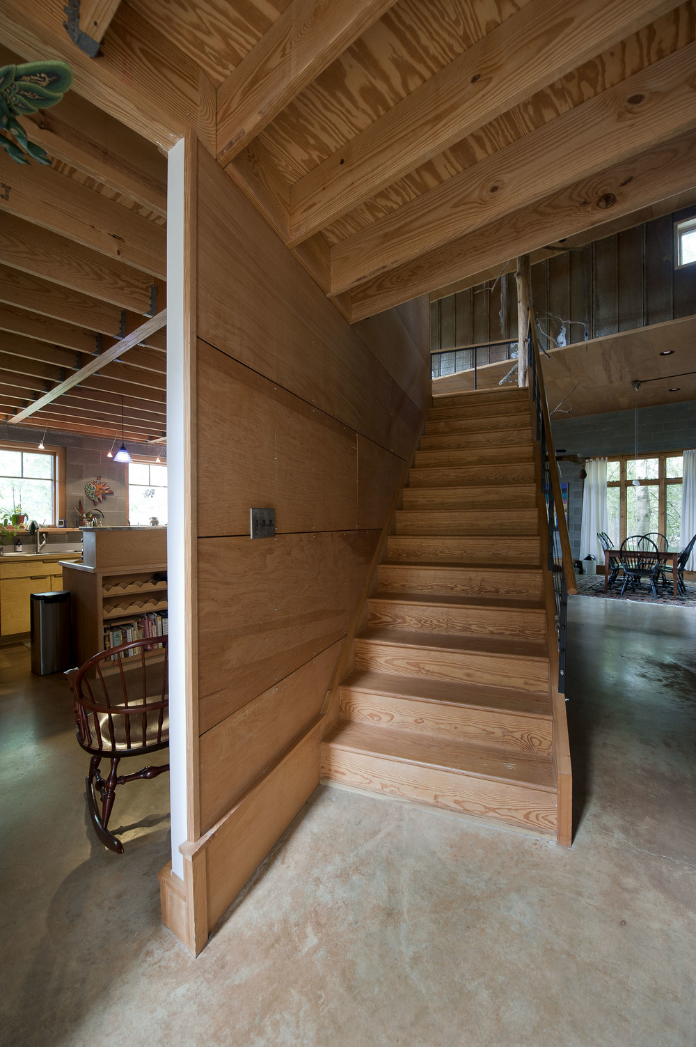 View from entrance encompasses kitchen, staircase, and living/dining area.