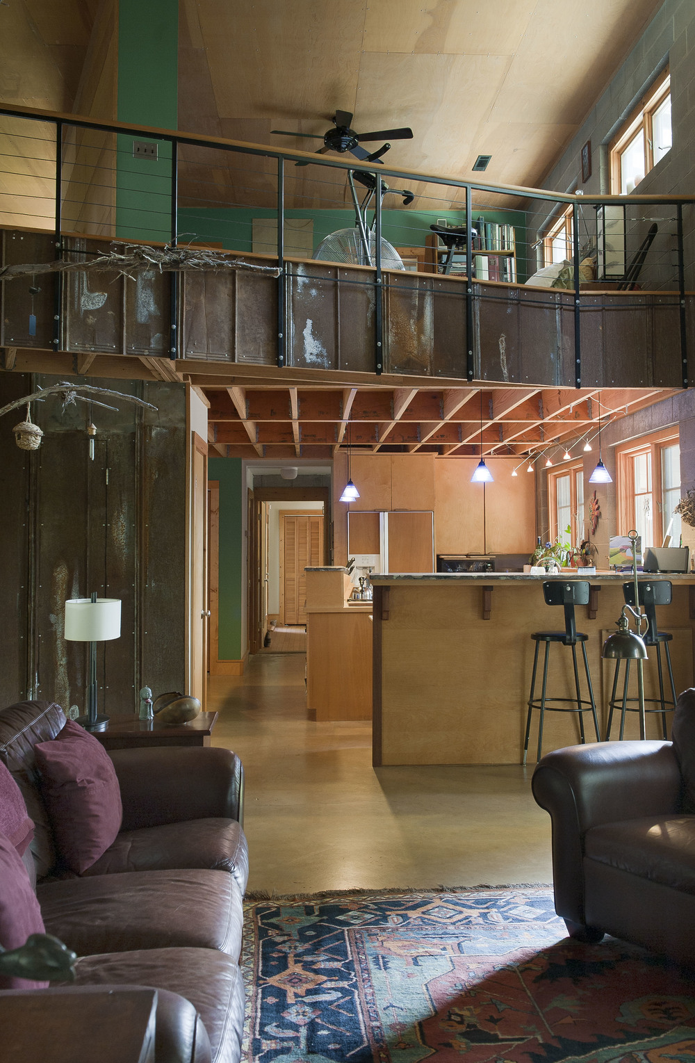 """The rustic master bedroom balcony and openness of the living and kitchen areas enhances the """"loft"""" design."""
