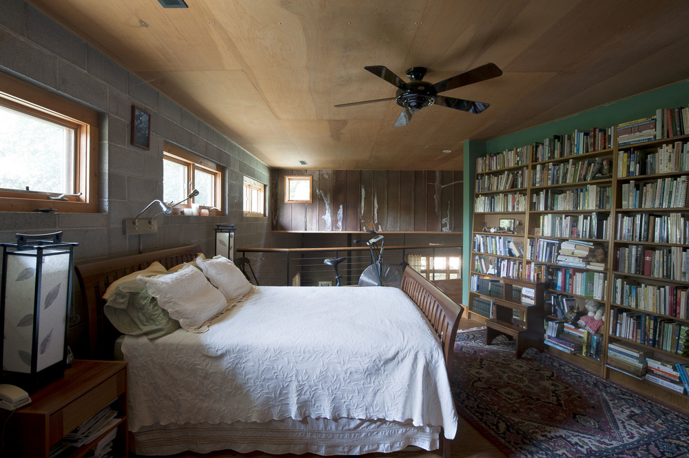 A long bookshelf wall and natural wood ceiling offer warmth to the master bedroom loft.