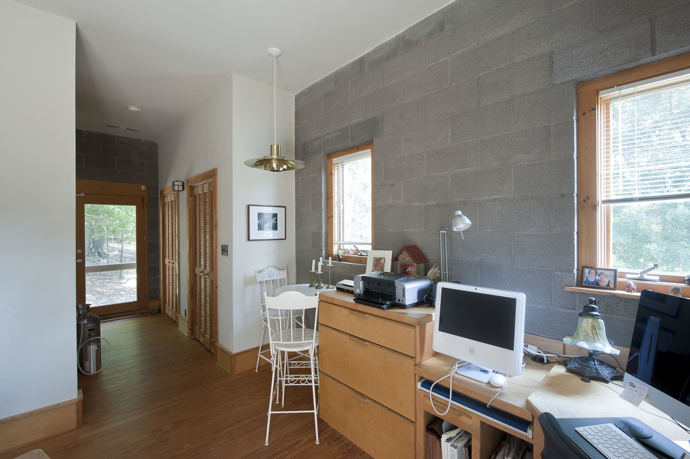 The office, separate from the open living area, is a quiet and bright space.