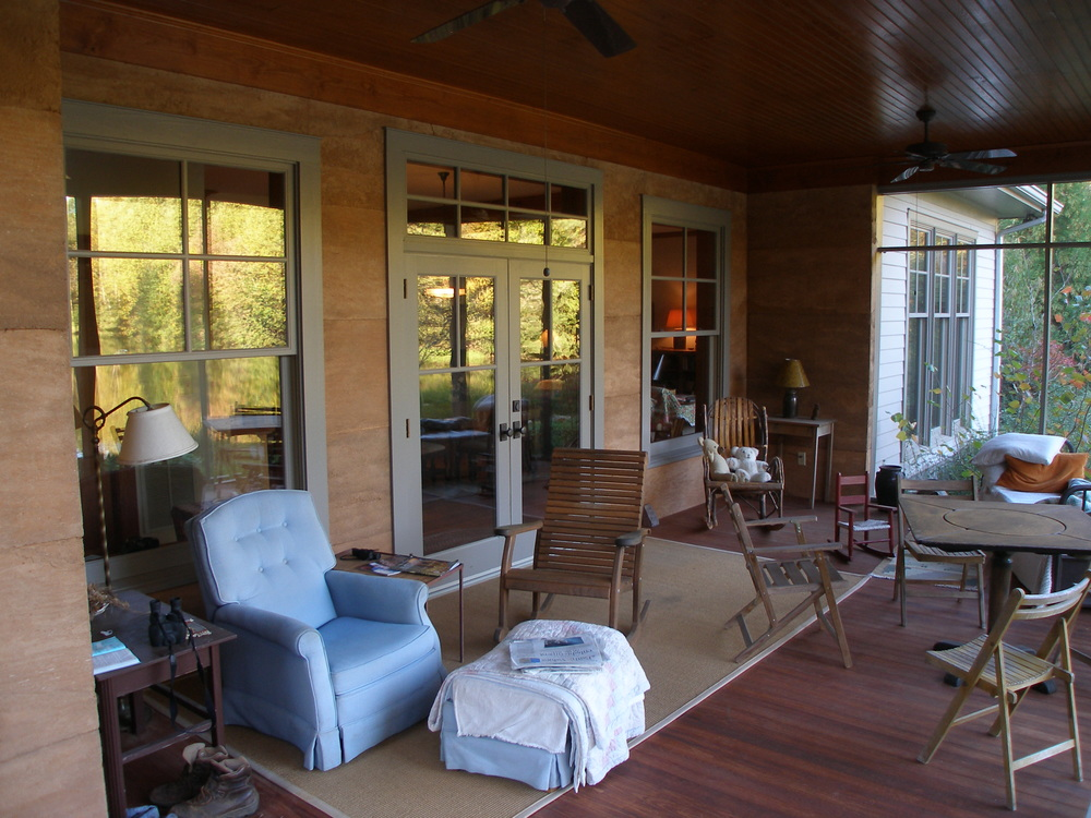 Screened in porch with rammed earth walls.