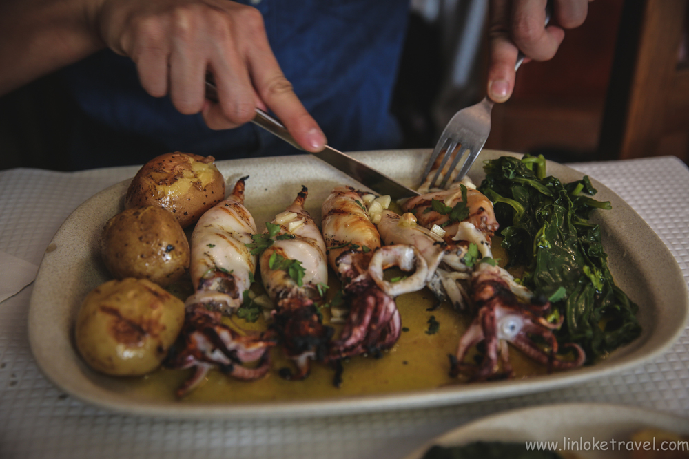 Food in Portugal/ Delicious grilled squid with a side of potatoes and greens.