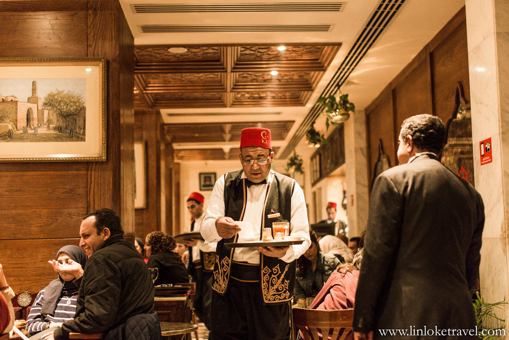 The waiters at Naguib Mahfouz Cafe are all clad in traditional uniforms and wear a red, tassled, felt cap (also known as 'Fez').