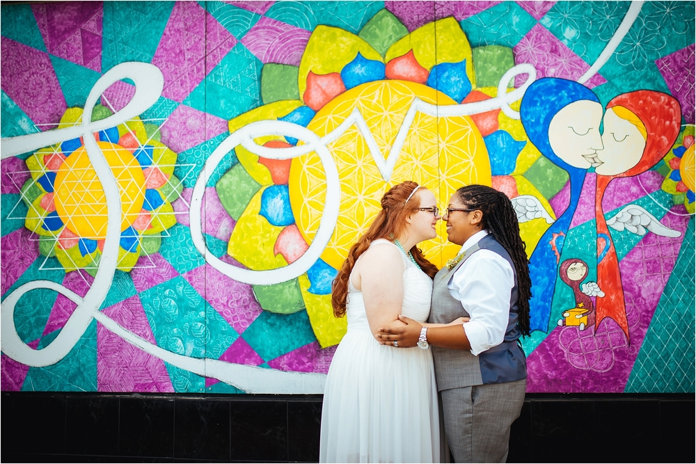 A Lovely Photo Wedding Photography embrace in front of mural