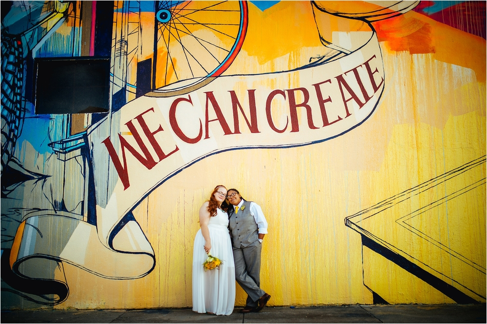 "A Lovely Photo Wedding Photography couple in front of mural reading ""we can create"""