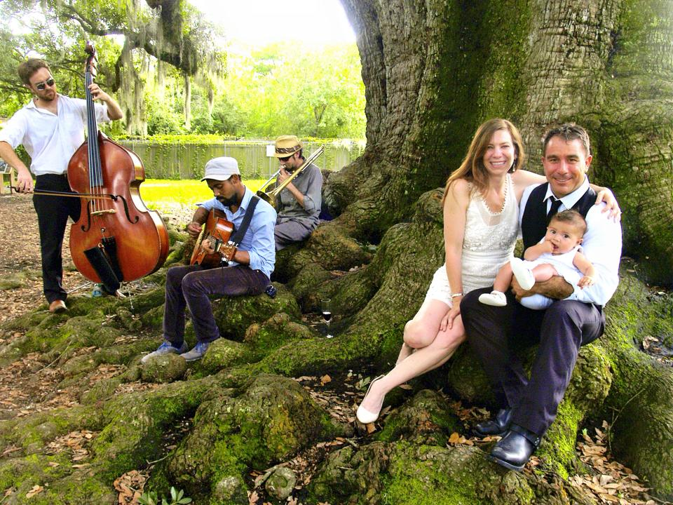 Couple and baby against tree with band playing nearby