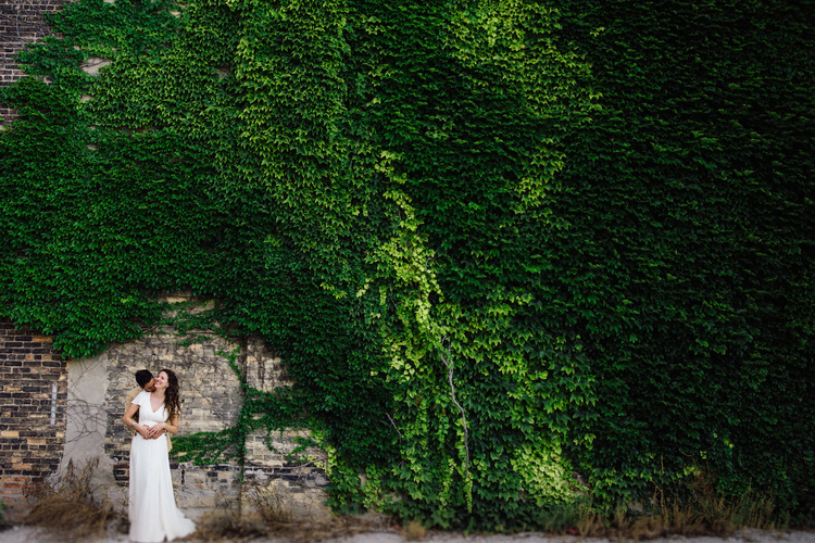Roost Wedding Photography embrace in front of leafy wall