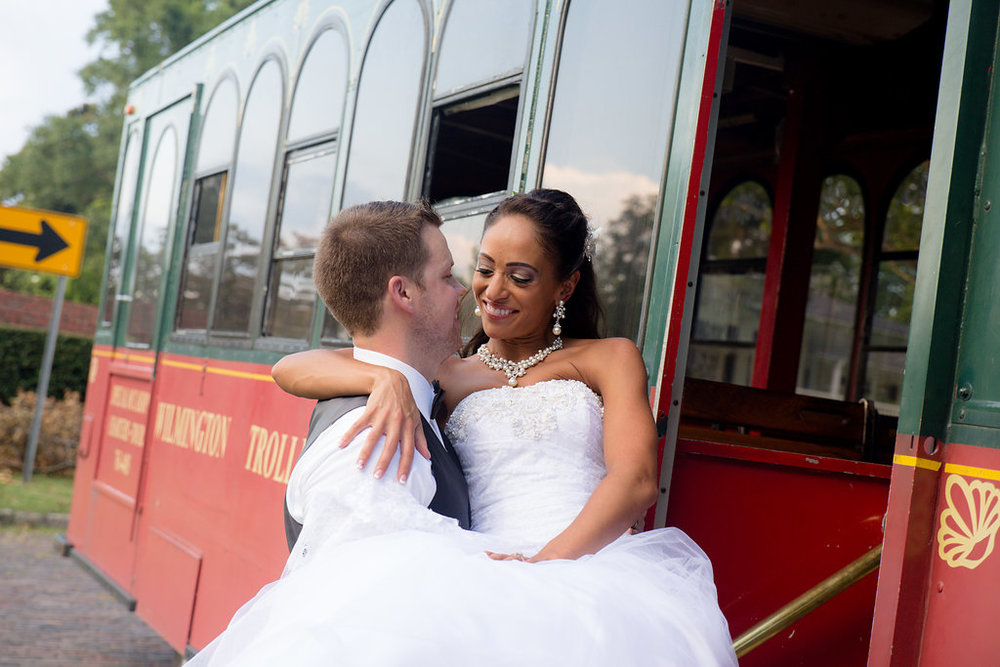 Megan Dickerson Wedding Photography North Carolina bride in groom's arms at trolley