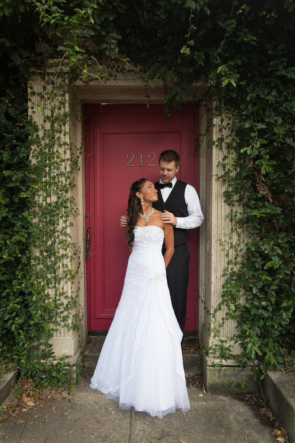 Megan Dickerson Wedding Photography North Carolina couple standing in doorway surrounded by eaves