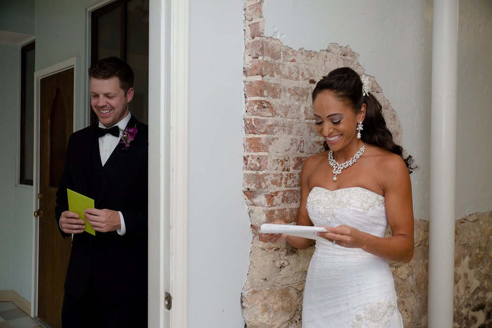 Megan Dickerson Wedding Photography North Carolina bride and groom separated by wall reading over vows