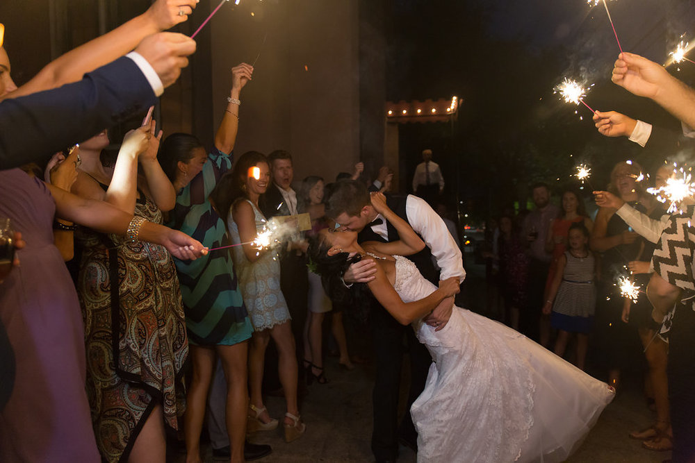 Megan Dickerson Wedding Photography North Carolina dip kiss surrounded by guests with sparklers