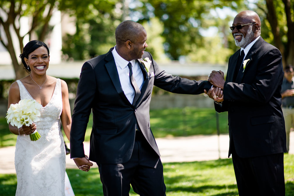 The Madious Wedding Photography DC bride and groom holding hands, groom shaking her father's hand