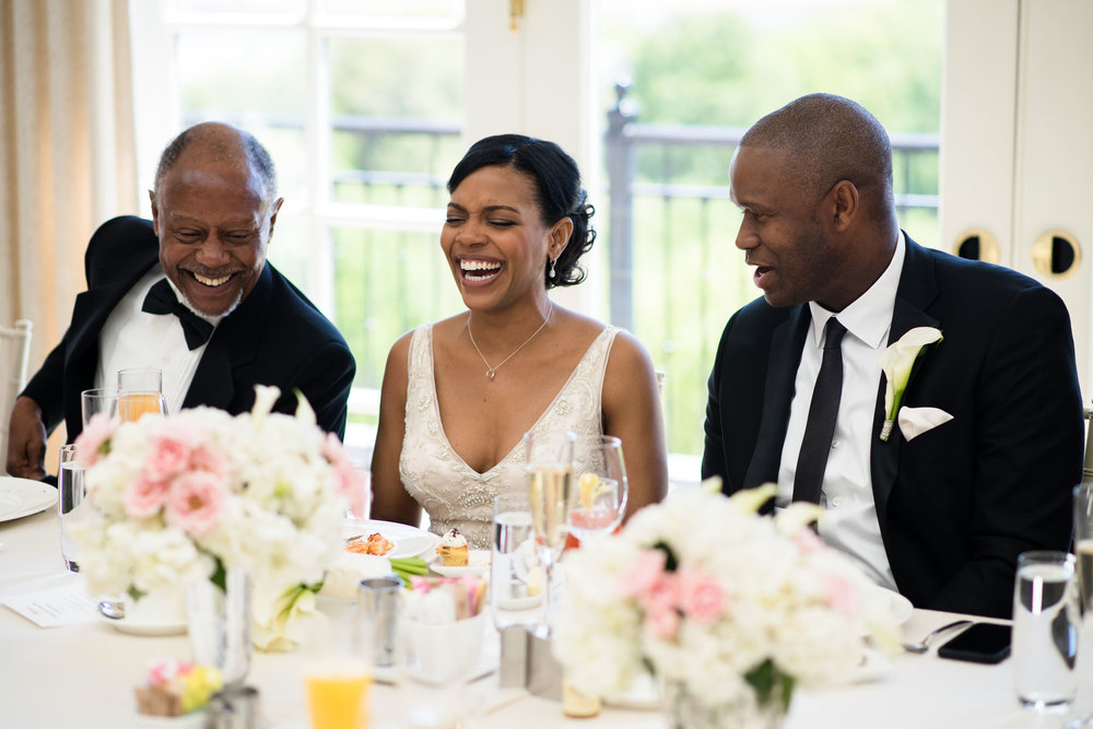 The Madious Wedding Photography DC bride, her father, and groom laughing at dinner table