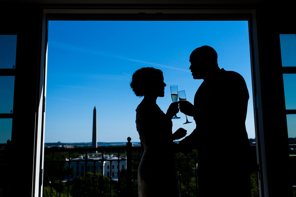 The Madious Wedding Photography DC silhouettes of couple holding champagne glasses