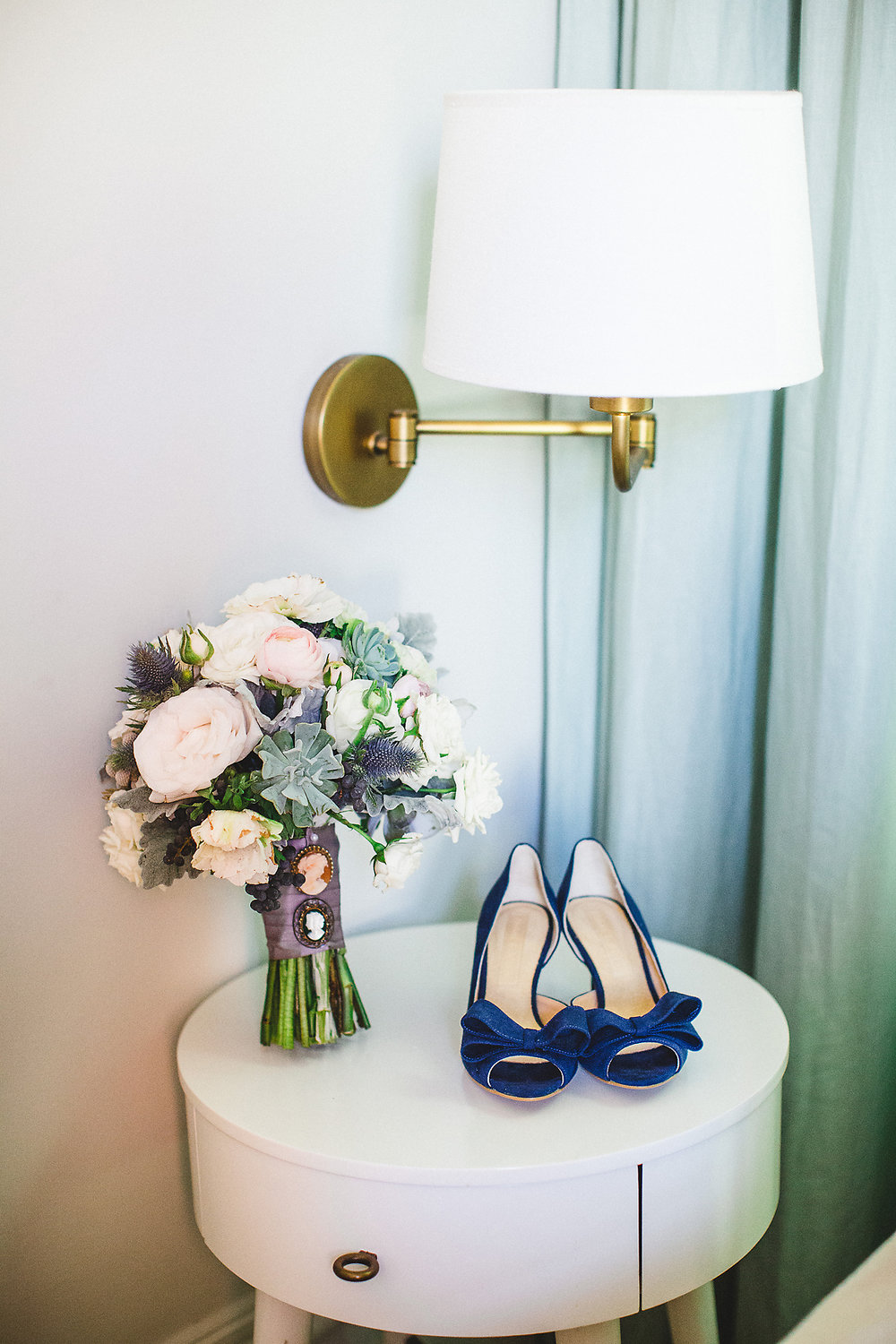 Izzy Hudgins Wedding Photography bride's shoes next to vase of flowers
