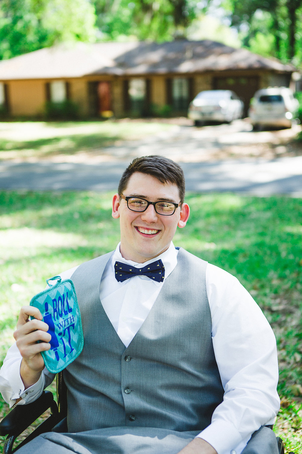 "Izzy Hudgins Wedding Photography groom in wheelchair holding potholder reading ""Roll With It"""