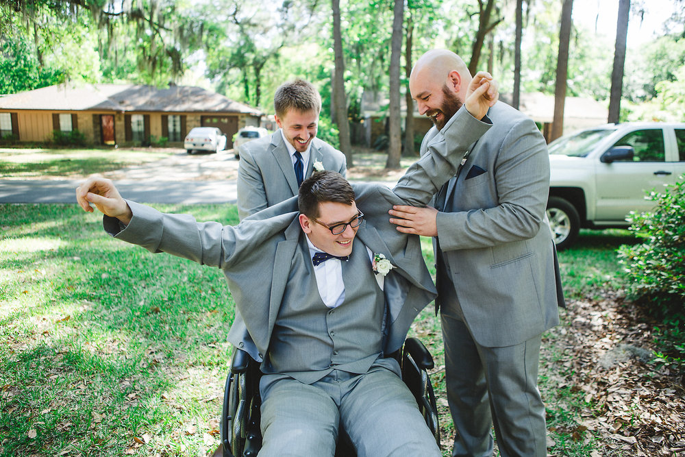 Izzy Hudgins Wedding Photography groomsmen assisting with groom's jacket